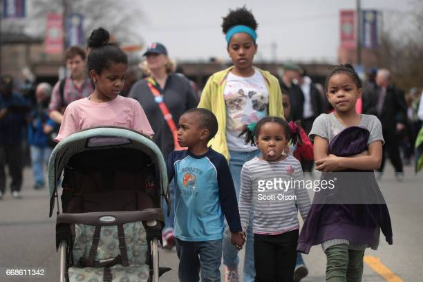 Children walk along as Cardinal Blase Cupich leads a march against violence in the Englewood neighborhood on April 14 2017 in Chicago Illinois The...