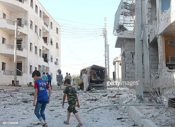 Children walk amid the debris of buildings destroyed when Syrian regime forces attack with barrel bombs in the Kafr Hamra District of northern Aleppo...