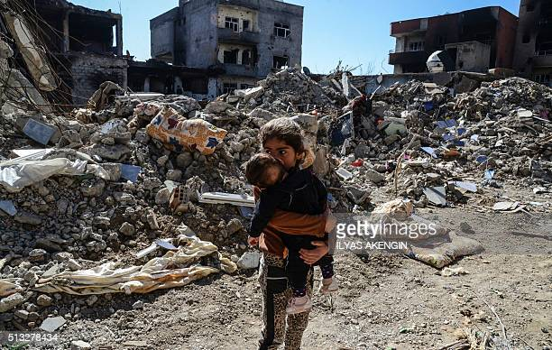 TOPSHOT Children walk among the rubble of damaged buildings following heavy fighting between government troops and Kurdish fighters in the Kurdish...