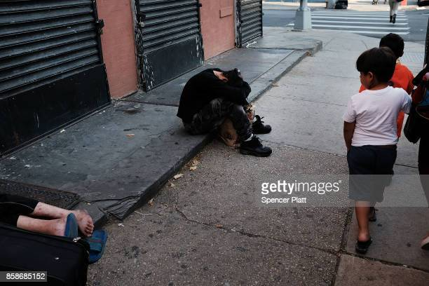Children walk by drug users passed out along a street in a South Bronx neighborhood which has the highest rate of heroininvolved overdose deaths in...