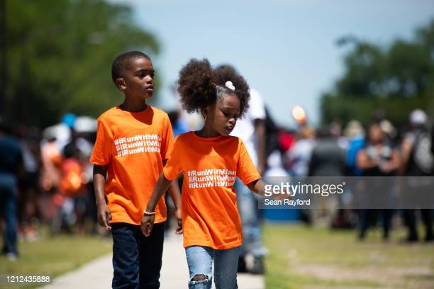 Children walk down a sidewalk as people gather to honor the life of Ahmaud Arbery at Sidney Lanier Park on May 9, 2020 in Brunswick, Georgia. Arbery...