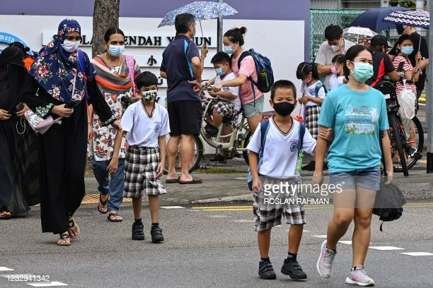 Children walk home with their guardians after school in Singapore on May 17 as the country prepares to shut all schools and switch to home-based...