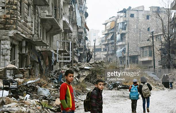 Children walk in a devastated area in the northern Syria city of Aleppo on Dec 13 as troops loyal to the government of President Bashar alAssad...