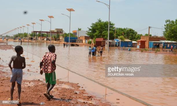 Children walk in a flooded street of Niamey following heavy rains on June 15 2017 At least nine children have been killed in Niger as heavy rains...