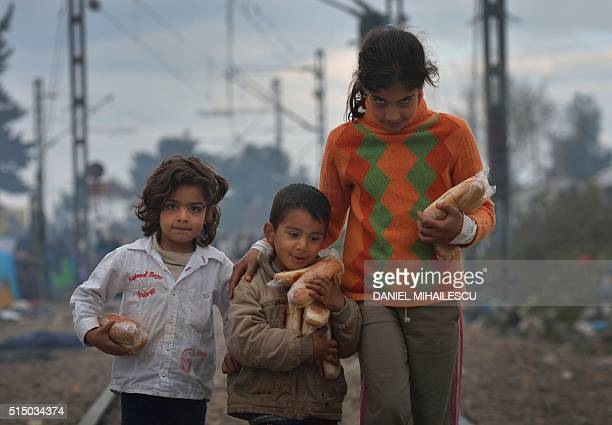 TOPSHOT Children walk in a makeshift camp on March 12 2016 at the GreekMacedonian border near the Greek village of Idomeni where thousands of...