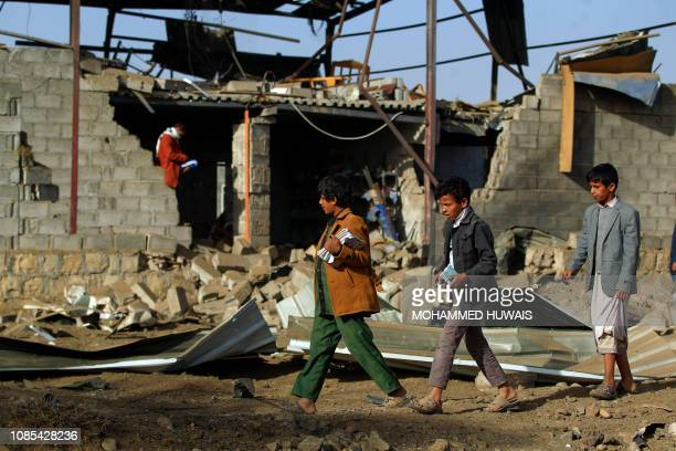 Children walk in front of the rubble of a destroyed factory after a reported airstrike by Saudiled coalition in the Yemeni capital Sanaa on January...