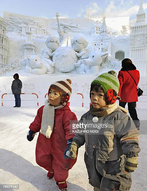 Children walk in front of the snow sculpture at the Odori park in central Sapporo on February 5 2008 The annual Sapporo Snow Festival kicked off...