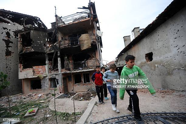 Children walk in the rubble of damaged houses after fighting between Macedonian police and an armed group in the town of Kumanovo on May 11 2015...
