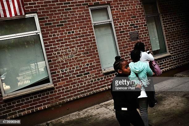Children walk into an East Harlem public housing complex on May 19, 2015 in New York City. New York City Mayor Bill de Blasio announced his 10-year...