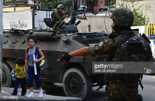 Children walk near soldiers at the Complexo do Alemao favela in Rio de Janeiro Brazil on August 22 2018 Rio de Janeiro's drug war hit a bloody...