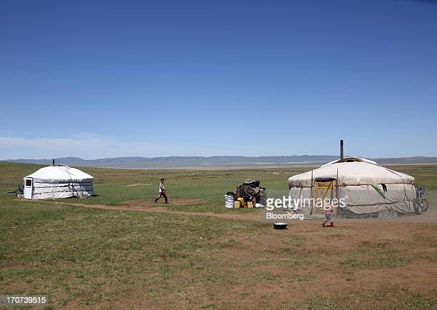 Children walk near their Gers in Zammar Mongolia on Tuesday June 11 2013 Mongolia a country of almost 29 million people is experiencing doubledigit...