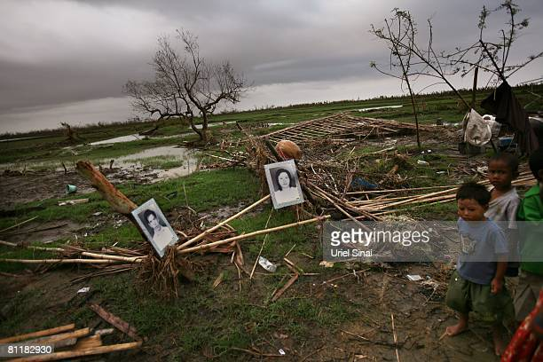 Children walk next to portraits of dead locals that are hung on what is left of their home on May 20 at the isolated village of Myasein Kan in the...