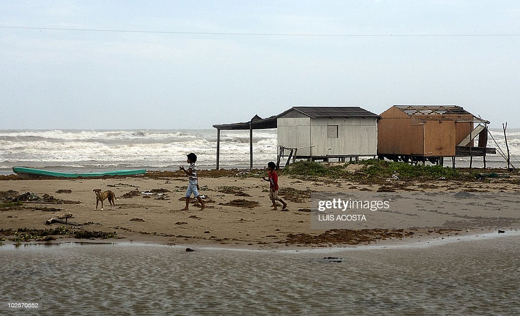 Children walk on a beach after the passage of Hurricane Alex in Bagdad Beach, in Matamoros, Tamaulipas State, on July 1, 2010. Alex, the first hurricane of the Atlantic season, weakened across northeast Mexico as it neared high mountains on Thursday, after disrupting oil clean-up operations in the Gulf of Mexico. Alex was downgraded to a tropical storm after roaring ashore late Wednesday as a Category Two hurricane slightly south of the eastern US-Mexico border. AFP PHOTO/Luis Acosta