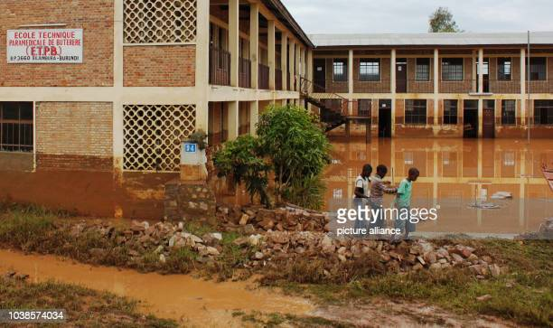 Children walk on a small dam between the flooded areas of the Buterere Paramedical School in Bujumbura capital of Burundi 10 February 2014 The number...