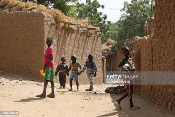 Children walk on a street in Niamey on December 21 2017 / AFP PHOTO / LUDOVIC MARIN