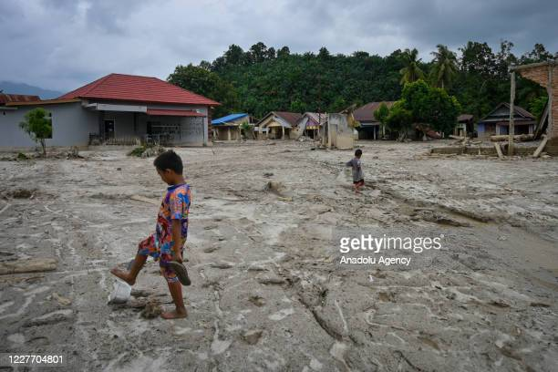 Children walk on mud in the Petambua residential area destroyed due to flash floods in North Luwu, South Sulawesi, Indonesia, on July 20, 2020. The...