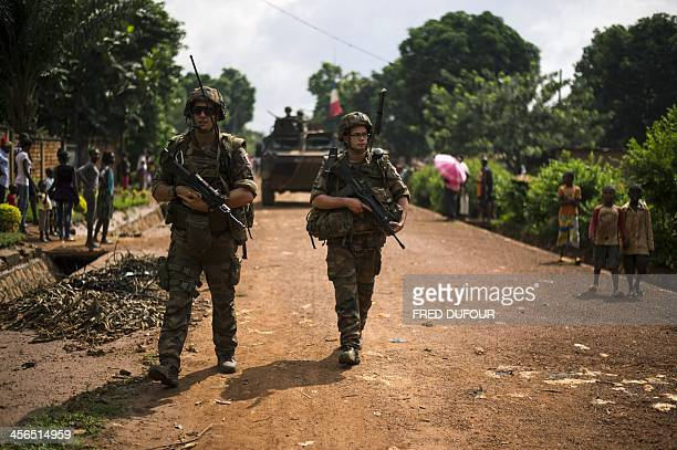 Children walk on the side of the road as French troops patrol in the streets of the Galabadja neighborhood in Bangui on December 14 as part of...