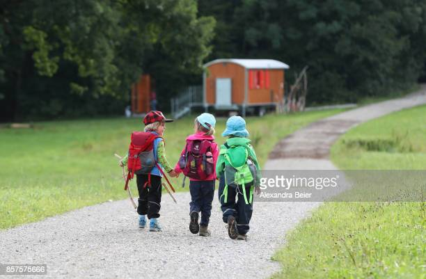 Children walk on the way to their forest kindergarten on July 31 2017 in Wessling Bavaria Germany The forest kindergarten is a preschool education...
