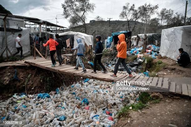 Children walk over a bridge in the Moria migrant camp on the Greek Aegean island of Lesbos on March 5, 2020. - Greece's defence ministry on March 5...