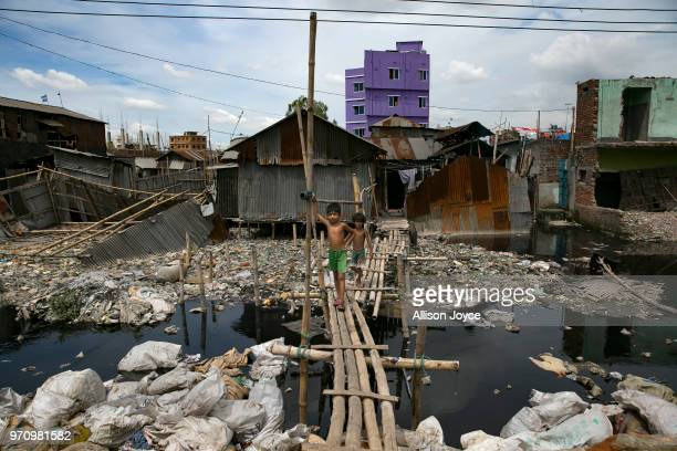 Children walk over a polluted canal that leads to the Buriganga river in Shyampur June 10 2018 in Dhaka Bangladesh Bangladesh has been reportedly...