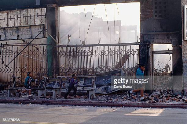 Children walk past a building destroyed by fire during the Los Angeles riots In April of 1992 after a jury acquitted the police officers involved in...