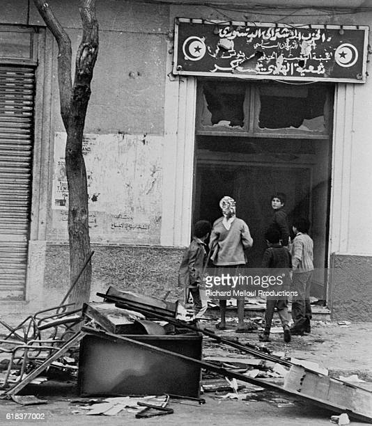 Children walk past a building with broken windows and streets littered with debris in Tunis A state of emergency was declared in the city after...