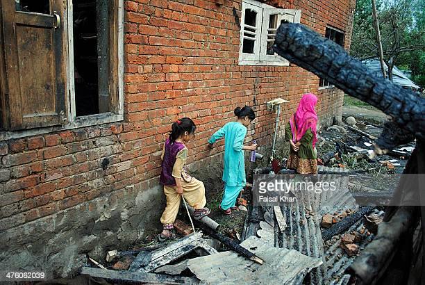 Children walk past a damaged house in yachgosa Shopian,Kashmir where two militants were killed in a 19 hour long fierce gun-battle between militants...