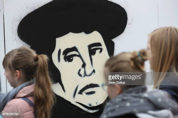Children walk past a graffiti artist's portait of Martin Luther at a fest on the main square celebrating Luther and 500 years since the Reformation...