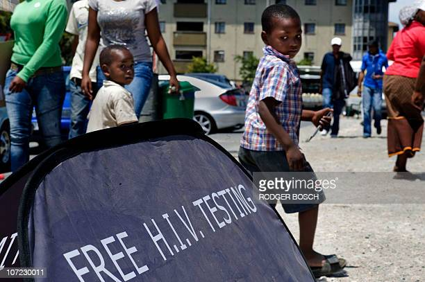 Children walk past a US funded mobile AIDS testing unit in Langa, a surburb of Cape Town, during the world AIDS Day on December 1, 2010. A million...