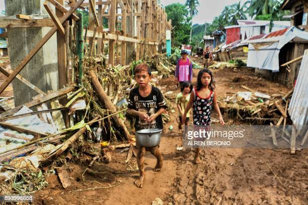 TOPSHOT Children walk past debris and damaged houses trees in Barangay San Mateo Borongan in eastern Samar on December 17 after Tropical Depression...