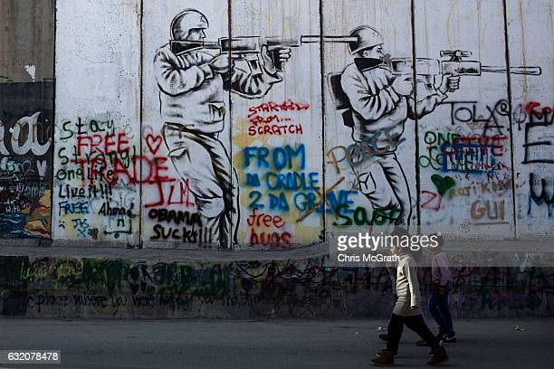 Children walk past graffiti painted on the Palestinian side of the separation wall on January 18, 2017 in Bethlehem, West Bank. 70 countries attended...