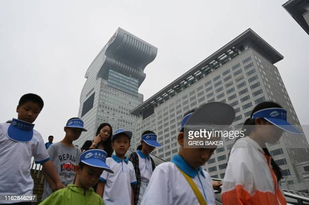Children walk past Pangu Plaza a skyscraper which dominates the area next to the Bird's Nest Olympic stadium in Beijing on August 20 2019 A Beijing...