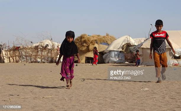 Children walk past tents at a displaced persons camp in the Khokha district of Yemen's western province of Hodeida, on May 6, 2020. - Almost six...