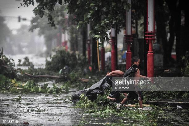 Children walk past uprooted trees along a highway as Typhoon Rammasun barrels across Manila on July 16 2014 Typhoon Rammasun shut down the Philippine...