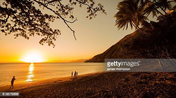 children walk the beach at sunset