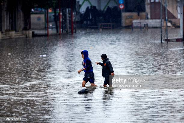 Children walk through a street flooded with rainwater at the Jabalia camp for Palestinian refugees in the northern Gaza Strip on December 17, 2020...