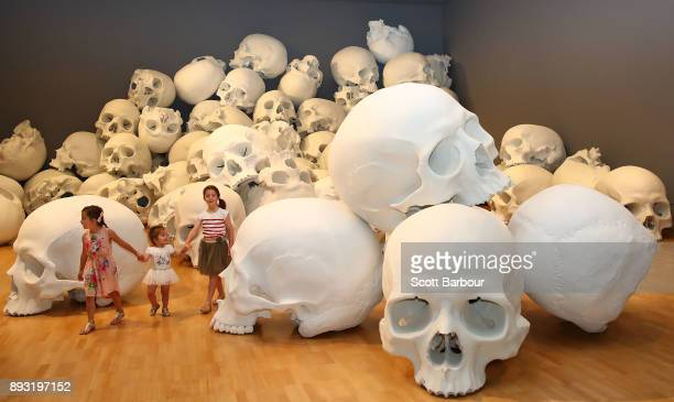 Children walk through artist Ron Mueck's worldpremiere installation 'Mass' consisting of 100 largerthanlife skulls each measuring 15m x 2m during a...
