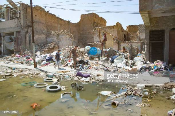 Children walk through debris in the destroyed old town in Mosul on April 24 2018 in MOSUL IRAQ