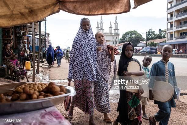 Children walk through streets of the popular neighbourhood of Bambeto in Conakry on September 18, 2021. - Guinea's ruling junta on September 18, 2021...
