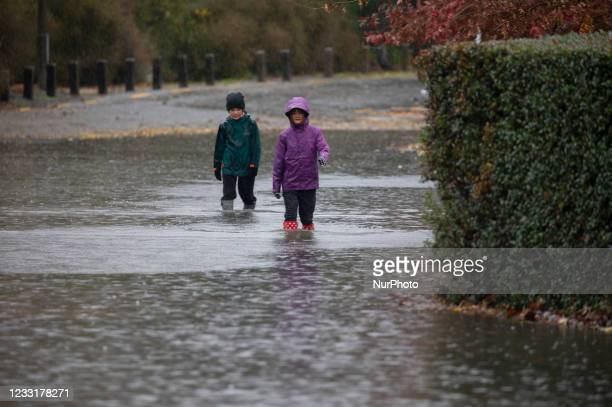 Children walk through the flood waters in Christchurch, NewZealand on May 30, 2021.MetService has put in place code red severe weather warning for...