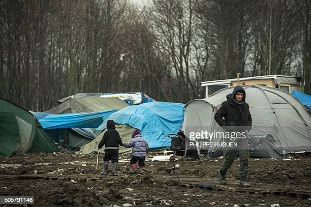 Children walk through the migrants camp of GrandeSynthe near Dunkirk on January 20 where almost some 2500 migrants and refugees live mostly Iraqi...