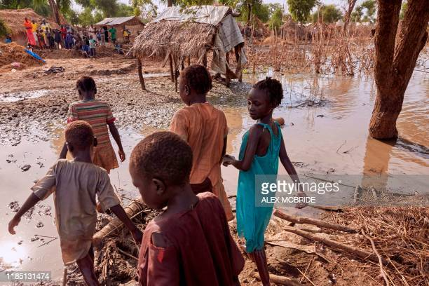 Children walk through the remaining flood waters in Yusuf Batir refugee camp in Maban South Sudan on November 25 2019 Large areas of eastern South...