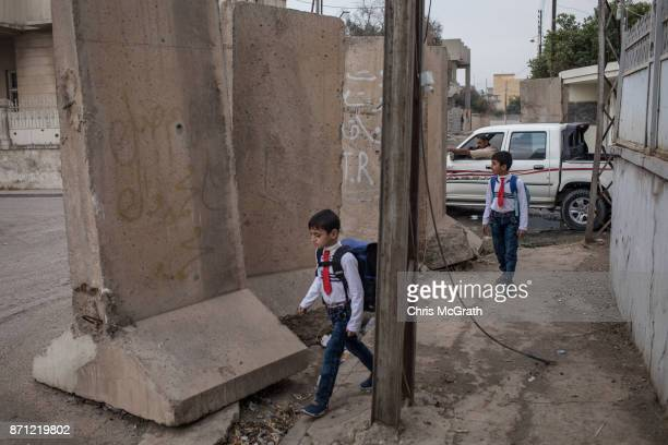 Children walk to school past blast walls in West Mosul on November 6 2017 in Mosul Iraq Five months after Mosul Iraq's secondlargest city was...