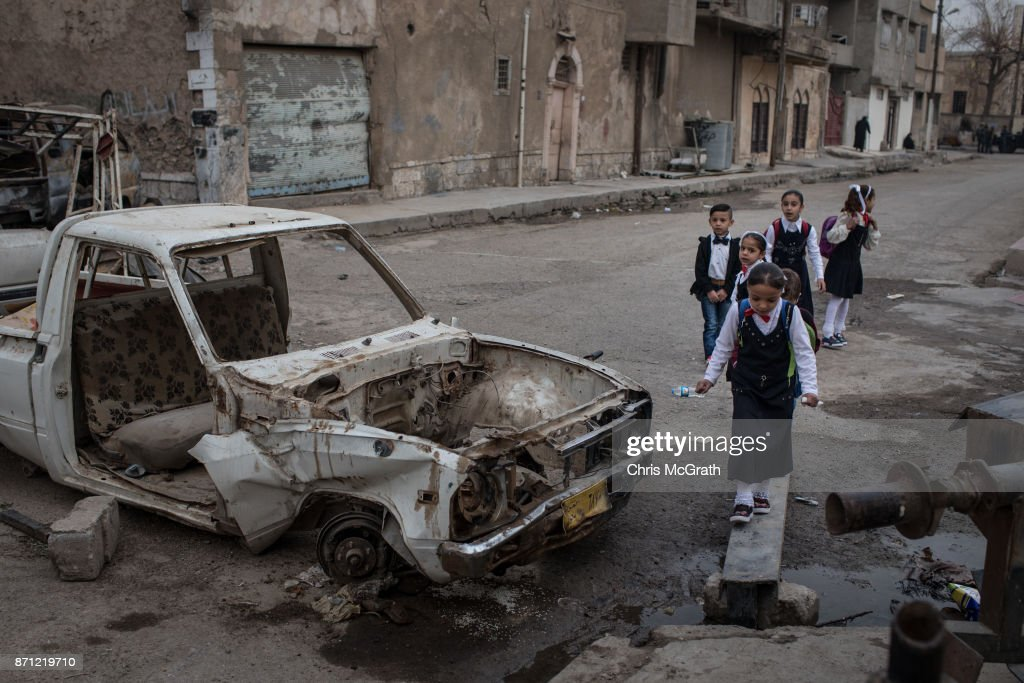 Children walk to school past destroyed cars in West Mosul on November 6, 2017 in Mosul, Iraq. Five months after Mosul, Iraq's second-largest city was liberated from ISIL in a nine-month long battle, residents have returned to the destroyed city to rebuild their lives. After more than two years of ISIL occupation, savage fighting, airstrikes and as ISIL fighters retreated they intentionally destroyed remaining key infrastructure such as bridges, government buildings, water and sewage facilities and neighborhoods laced with booby traps and homemade bombs leaving the city in ruins. Despite the damage residents have hastily returned and managed to setup temporary shops, homes and services to help bring the city back to life. In West Mosul, home to the Old City, more than 32,000 homes were destroyed and a recent report from the U.N. estimates repairing Mosul's basic infrastructure will cost more than $1 billion and take years to complete.