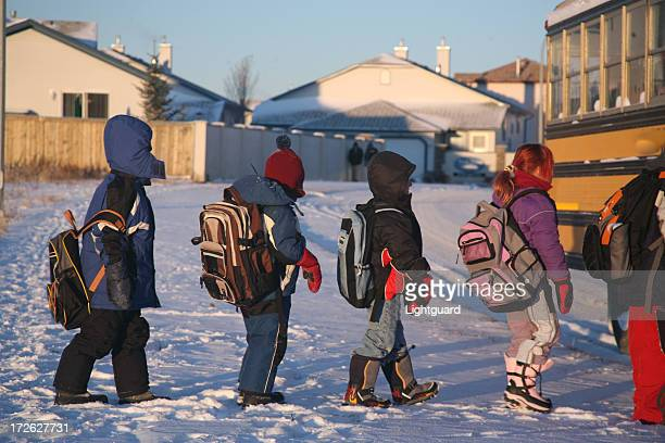 Children walk to the school bus on a winter day
