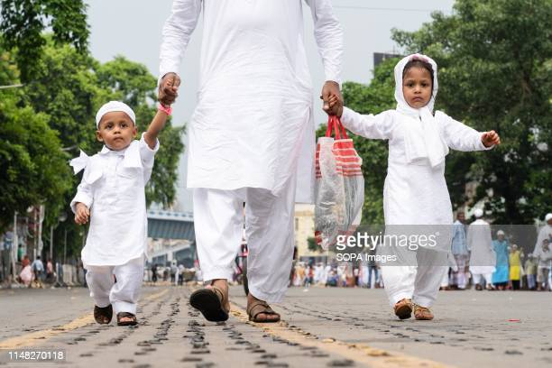 Children walk with their father headed for Eid al Fitr prayers to mark the end of the holy fasting month at park circus in kolkata India Muslims...