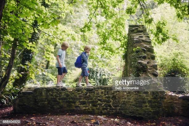 Children walking along a wall