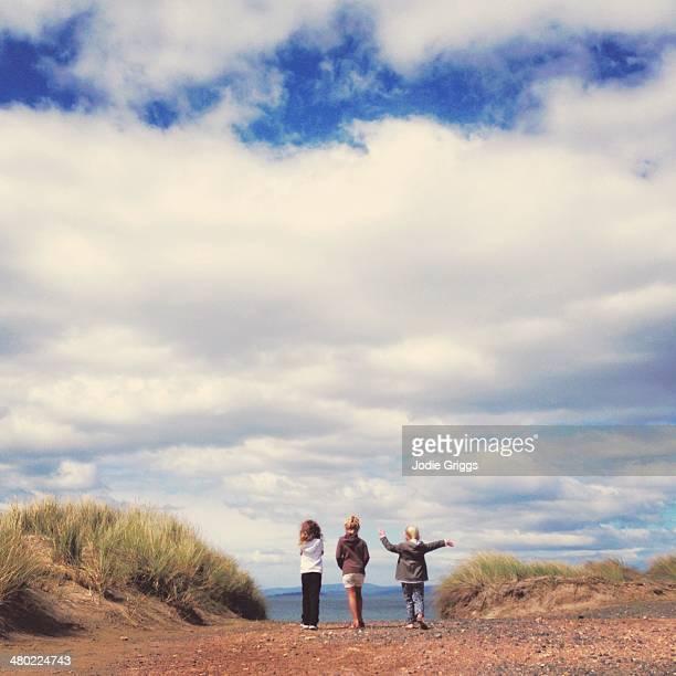 Children walking down dirt road towards beach