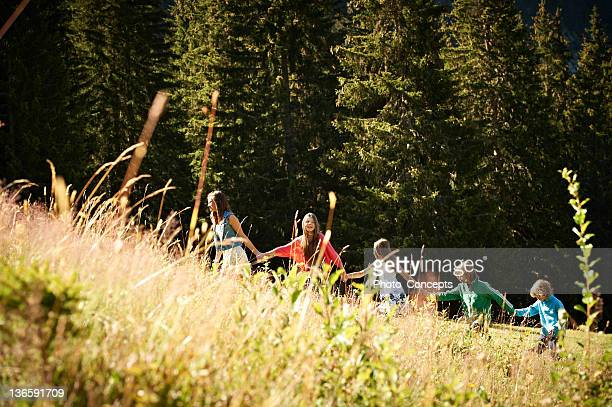 children walking holding hands in field - following stock pictures, royalty-free photos & images