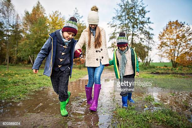 Children walking in a puddle in autumn
